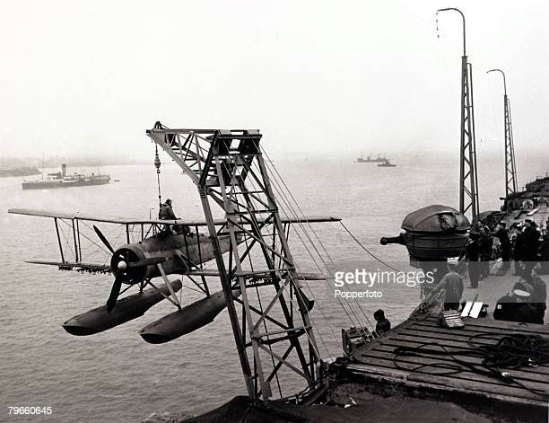 World War II circa 1940 A Fairey Swordfish biplane torpedo bomber is hoisted aboard Royal Navy aircraft carrier HMS Ark Royal during its refit at...