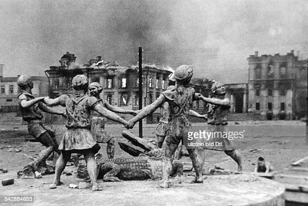 World War II eastern front Stalingrad sculpture of dancing children of a destroyed fountain in the background burning ruins Picture taken by Emmanuil...