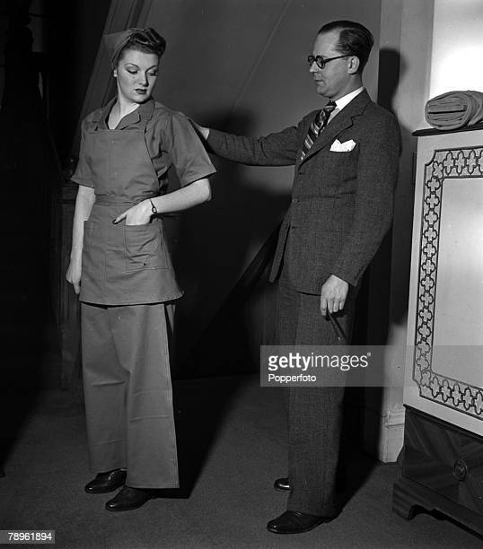 World War II England British fashion designer Digby Morton is pictured with a model wearing one of his designs a munition workers outfit