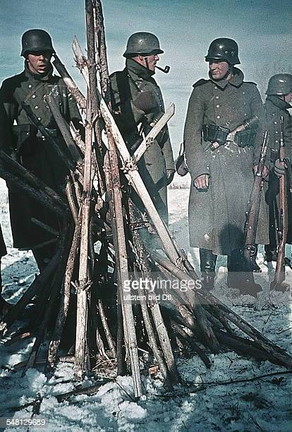 World War II German soldiers at the Eastern Front warming themselves at a fire no place given winter 1941/42 Photographer Artur Grimm