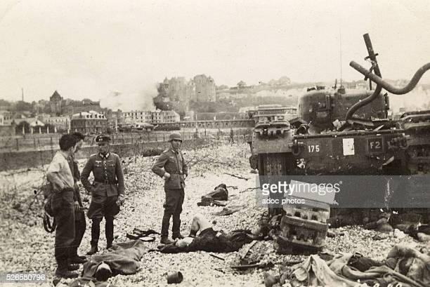 World War II. German soldiers near the dead bodies of Canadian soldiers on the beach at Dieppe . In Augsut 1942.