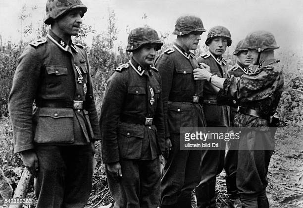 World War II Latvia: in the Latvian sector, regiment marshal venerating five 'Unterfuehrern' the 'Eiserne Kreuz 2. Klasse '- 1944- Photographer:...