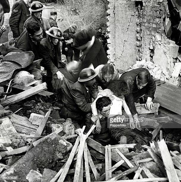 World War II London England 1940's Home Front Rescue workers pulling out injured victims from a pile of rubble after a building was dstroyed by heavy...