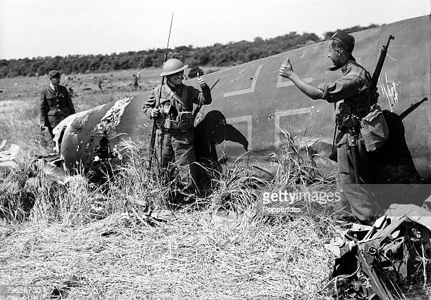 19th June 1940 British soldiers stand guard on a German Luftwaffe bomber shot down over eastern England as they give the thumbsup sign