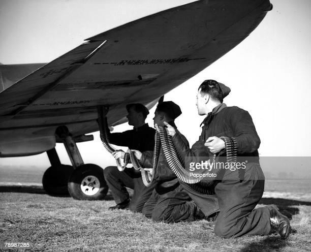 World War II RAF Fighter base England Mechanics with a long belt of ammunition feeding the guns of a spitfire