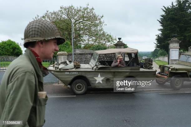 World War II reenactors including one calling from his cell phone while sitting in a World War IIera American amphibious jeep gather on June 04 2019...