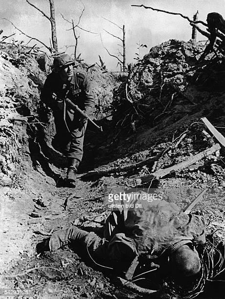 World War II. ; Russia: german soldier walking trough a dugout; in front a dead russia soldier - taken by Schmidt-Scheeder