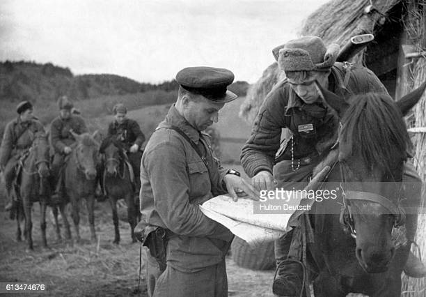 A World War II scout for the Red Army points out important information on his map while his detachment commander observes