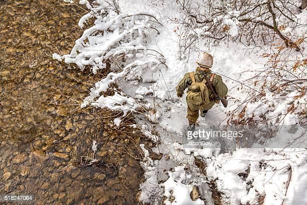 World War II: Soldier Crossing Creek in the Snow
