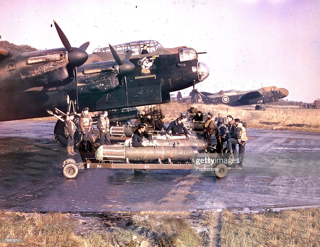 World War II. 1942. The crew of Lancaster bomber +Admiral Prune+ stands by as their plane is prepared for a mine-laying operation. : News Photo