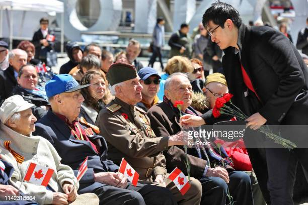 World War II veterans from the Red Army are given flowers during celebrations for Victory in Europe Day at Nathan Philips Square in Toronto, Ontario,...