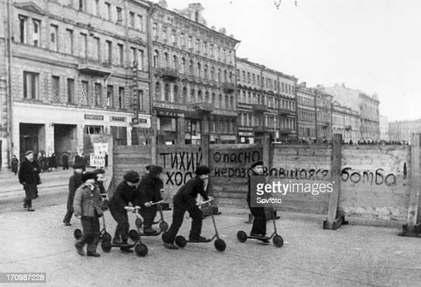 'drive slowly unexploded bomb danger' says the notice painted on the fence in the foreground leningrad children have organized scooter races they...