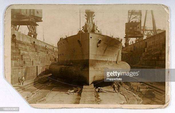 A World War One battleship in dry dock showing an unusual shaped hull featured on a vintage postcard produced circa 1916
