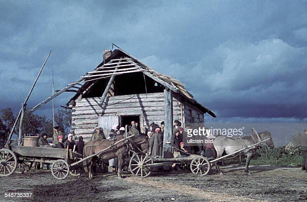 2 World War Soviet Union german occupationhorsedrawn carts and a cottage at a lakeshoreabout 1943