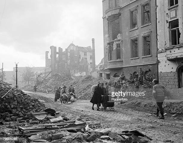 World War Two 15th October 1944 Germany Civilians in the German town of Aachen walk through the destroyed streets and houses as American troops look...
