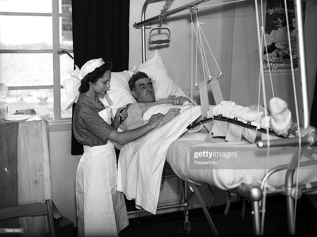 World War Two. England. 7th August, 1940. A nurse takes the pulse of a young soldier as he rests in bed a war hospital where wounded men are nursed back to health. : News Photo