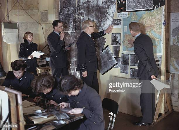 World War Two February Bomber command chief Arthur 'Bomber' Harris looking at aerial reconnaisance photographs and maps of strategic sites in the...