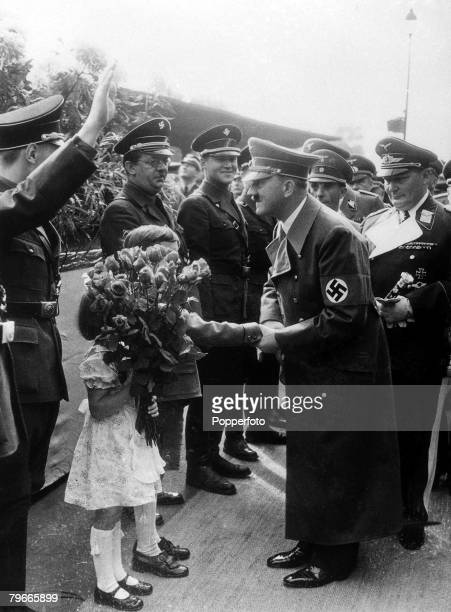 World War Two Germany 2nd October 1938 German Chancellor and Nazi dictator Adolf Hitler receives flowers from children in Munich watched by Field...