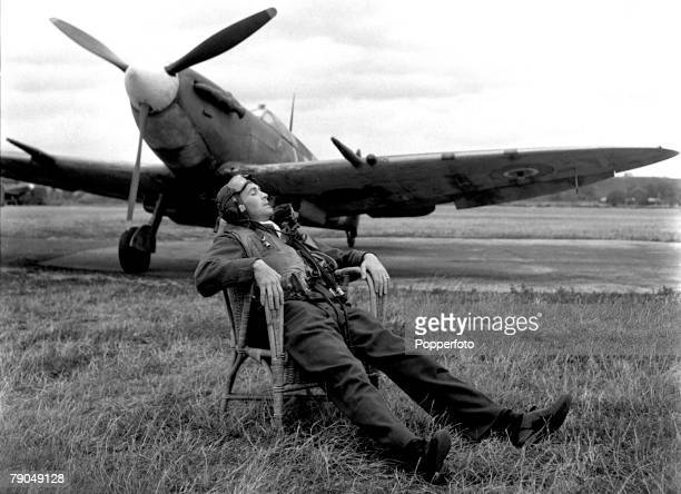 World War Two RAF Base Somewhere in England A pilot in full uniform ready to respond to orders takes a moment to relax in a wicker chair placed near...