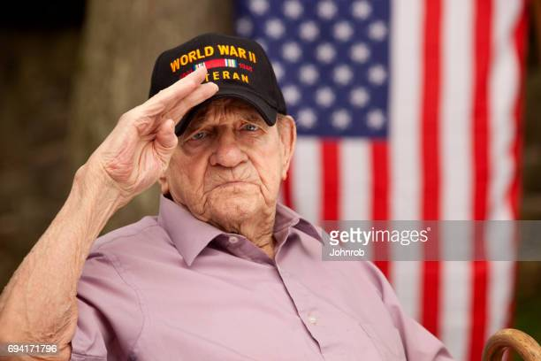 World War Two, Veteran wearing baseball cap with text, 'World War Two Veteran'. Saluting