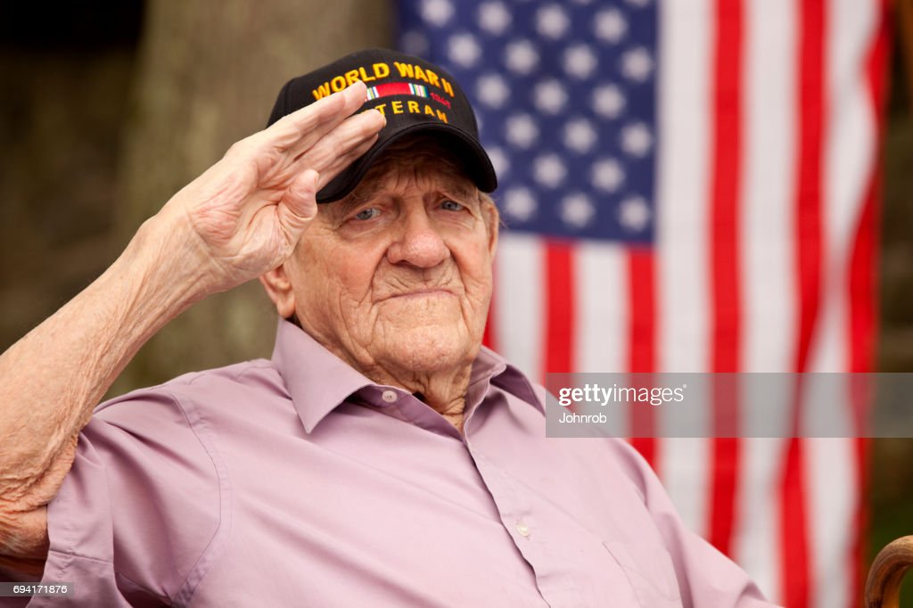 """World War Two, Veteran wearing cap with text, """"World War Two Veteran"""". Saluting : Stock Photo"""