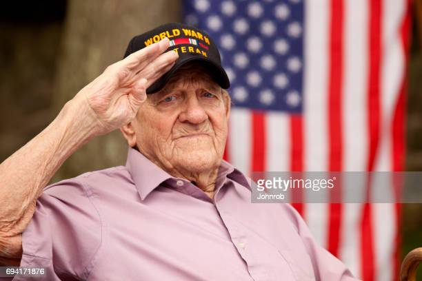 "World War Two, Veteran wearing cap with text, ""World War Two Veteran"". Saluting"