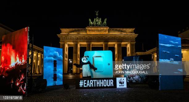 World Wide Fund for Nature activist dressed in a Panda suit prepares to symbolically throw a giant switch to turn off the illumination of Berlin's...