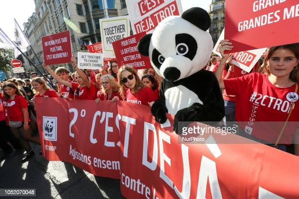World Wide Fund for Nature members holding signs and banners take part in a march against climate change in front of the Paris Opera on October 13...