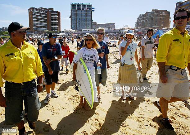 World Women's Champion Lane Beachley of Australia walks down to the water watched by two security guards for the start of her heat which included...