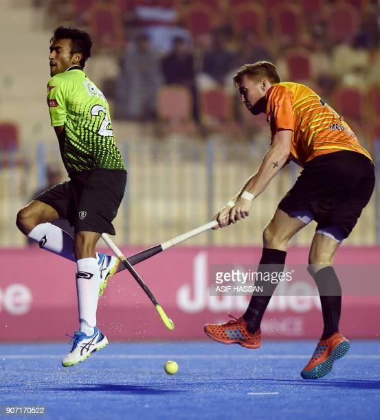 World XI field hockey player Philip Meulenbroek vies Pakistani player Rizwan Ali during their first match at the Abdul Sattar Edhi hockey stadium in...