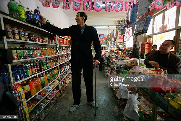 World's tallest man Bao Xishun arranges goods for a supermarket as he shops on March 30 2007 in Chifeng of Inner Mongolia Autonomous Region China The...