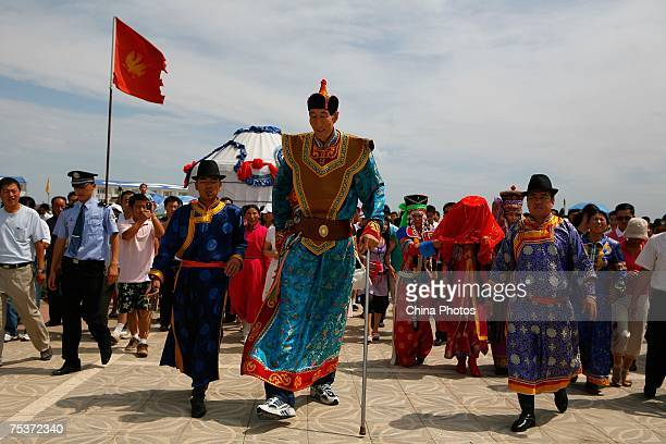 World's tallest man Bao Xishun walks to meet his bride Xia Shujuan during their traditional Mongolian wedding ceremony at Genghis Khan's Mausoleum on...