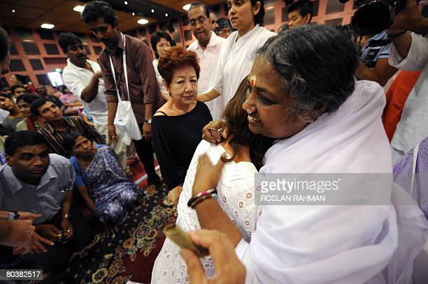 Worldwide known as the 'Hugging Saint' humanitarian Mata Amritanandamyi receives a hug from believers at the Singapore Expo hall in Singapore on...