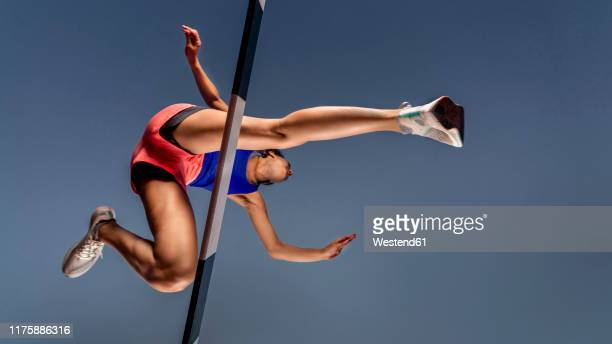worm's eye view of female runner crossing hurdle - hurdling horse racing stock pictures, royalty-free photos & images