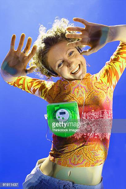 worms eye view of young woman laying on clear plastic flooring, listening to portable cd player and making faces - personal compact disc player stock pictures, royalty-free photos & images