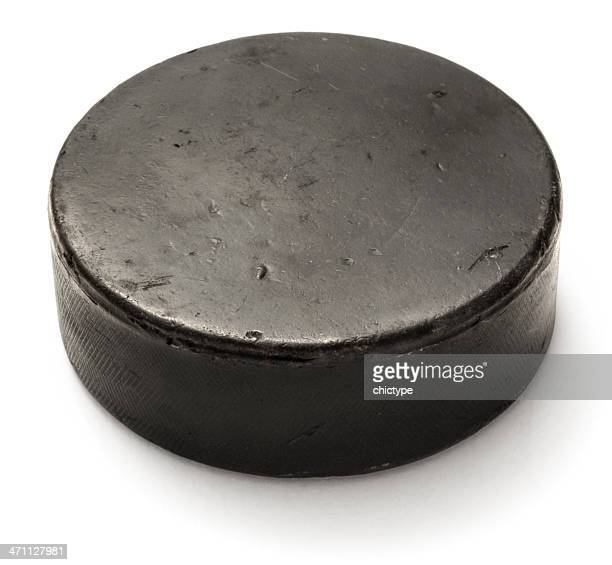 Worn black hockey puck on white background