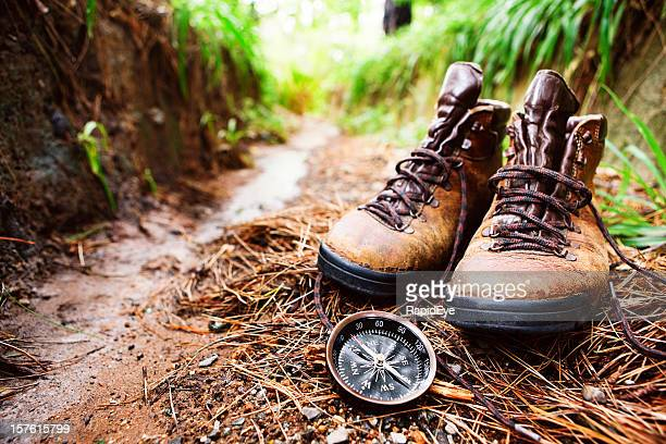 Worn hiking boots and compass on muddy walking trail
