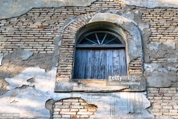 Worn out brick wall with a weathered wooden window on an old building, Santa Clara, Cuba