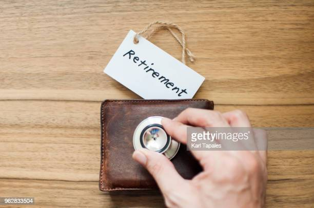 a worn out wallet with stethoscope - ricchi e poveri foto e immagini stock