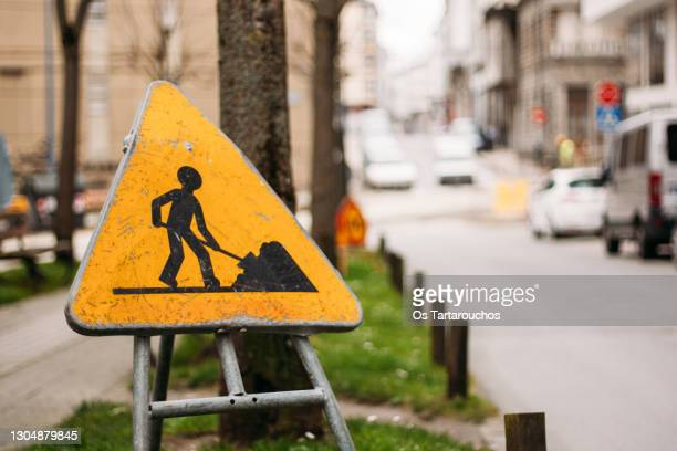 worn temporary works sign on a city street - warning sign stock pictures, royalty-free photos & images