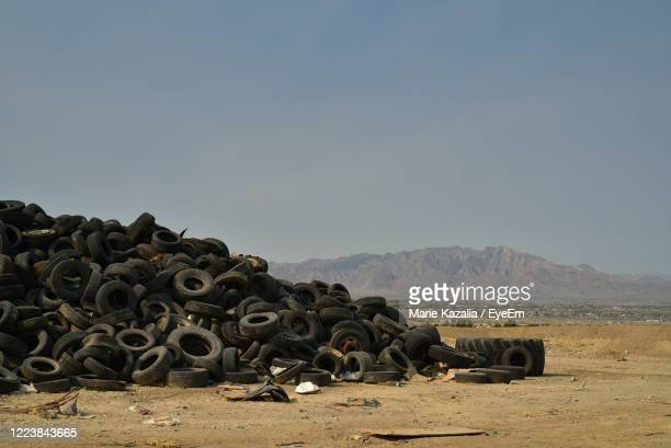 worn-out vehicle tires piled in mojave desert with distant mountains in pahrump, nevada, usa - ゴミ捨て場 ストックフォトと画像