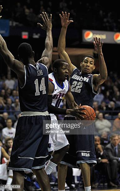 Worrel Clahar of the DePaul Blue Demons passes between Henry Sims and Otto Porter of the Georgetown Hoyas at Allstate Arena on January 17 2012 in...