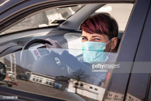 worried adult woman driving to shop wearing n95 face mask and protective gloves during covid-19 outbreak - stock photo - driving mask stock pictures, royalty-free photos & images
