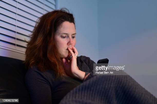 worried adult woman using mobile photo - rafael ben ari stock pictures, royalty-free photos & images
