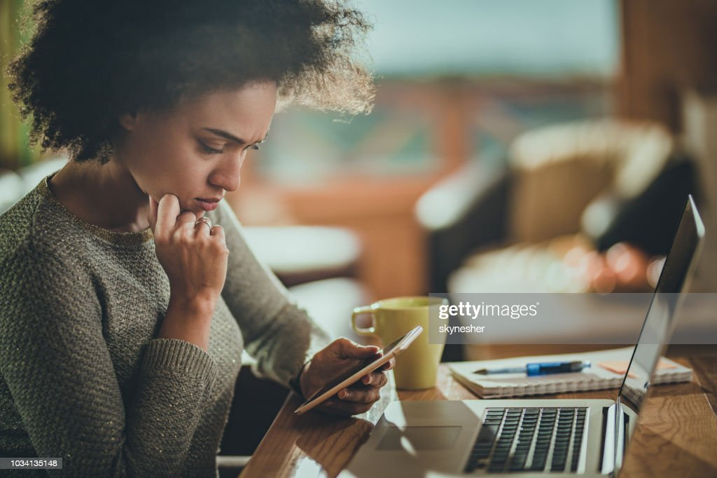 Worried African American woman using cell phone while working at home. : Stock Photo