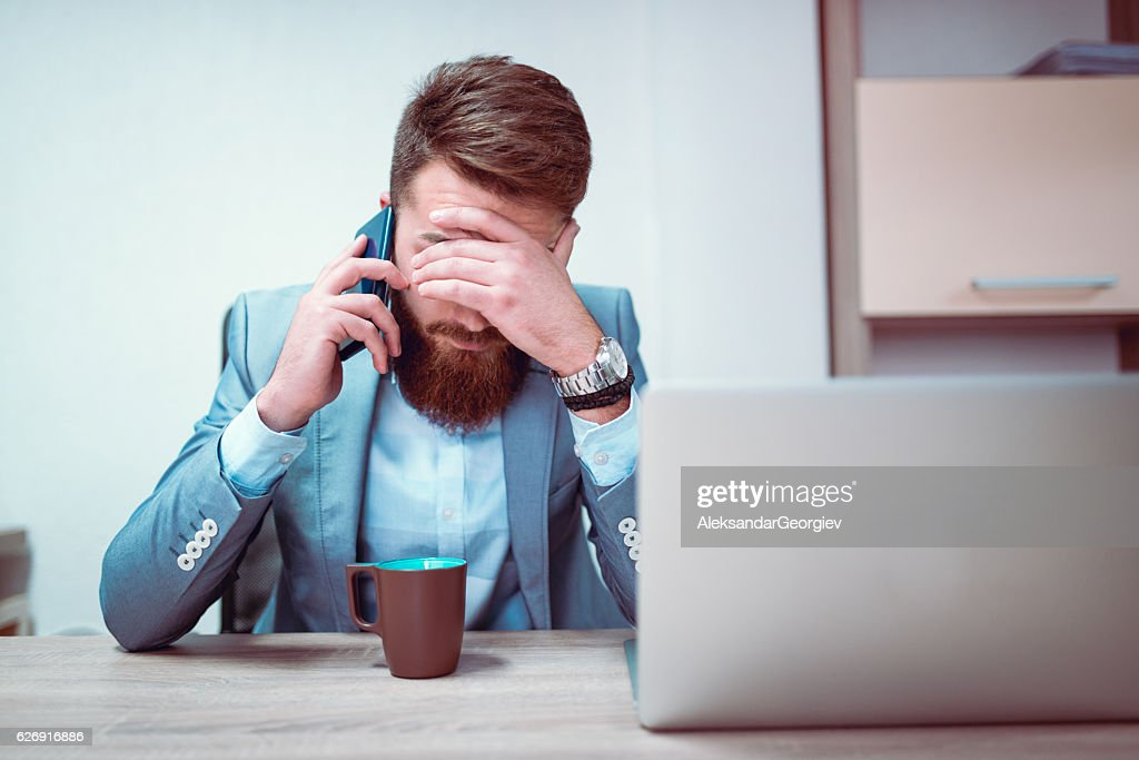 Worried and Exhausted Businessman Talking on Phone in his Office : Stock Photo