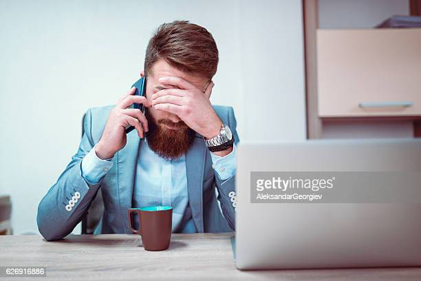 worried and exhausted businessman talking on phone in his office - preocupado - fotografias e filmes do acervo