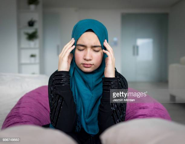 worried and nervous muslim girl - uncomfortable stock pictures, royalty-free photos & images