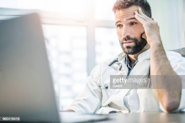 bang en moe medio volwassen mannelijke arts lezen van medische resultaten op zijn laptop. - negatieve emotie stockfoto's en -beelden
