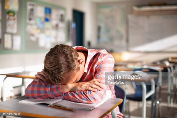 worried and tired teenage student resting on book at desk - school detention stock pictures, royalty-free photos & images